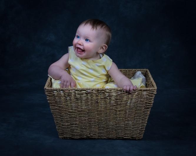 Happy baby girl in wicker basket studio portrait