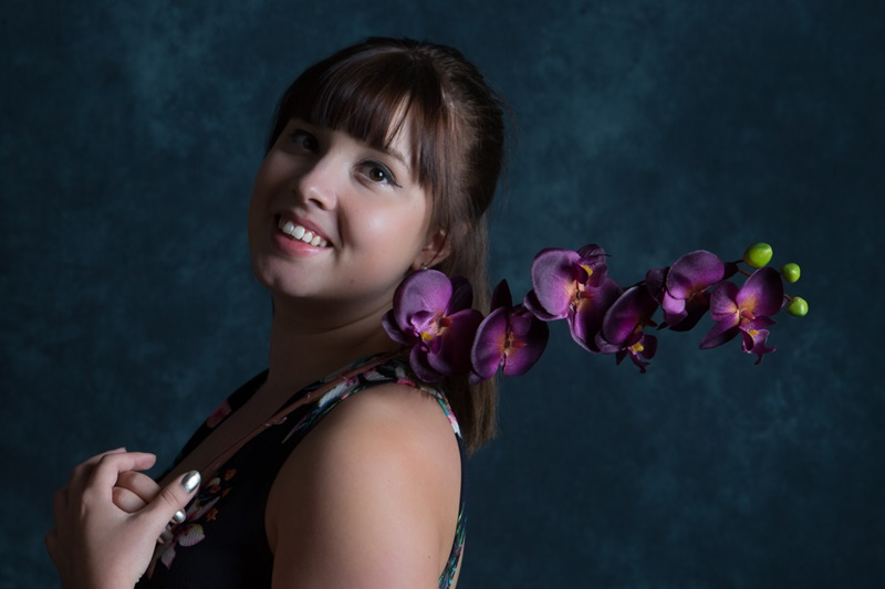 Beautiful young woman posing with purple flowers in studio