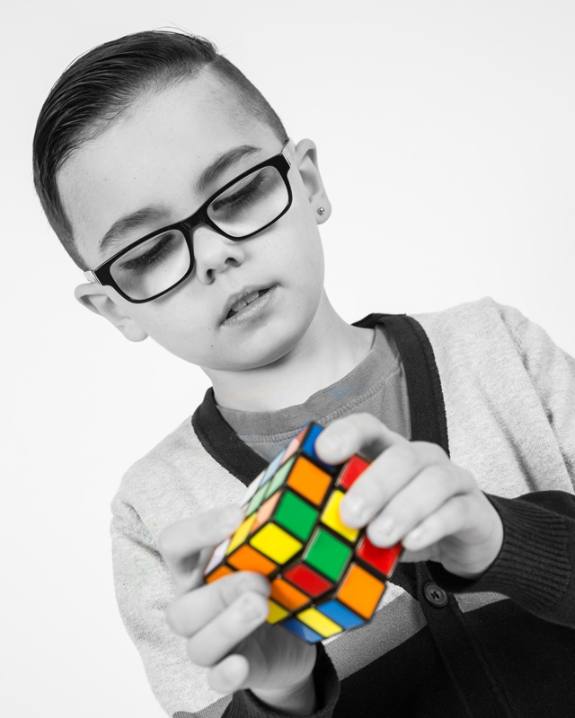 Boy with glasses and rubiks cube studio portrait