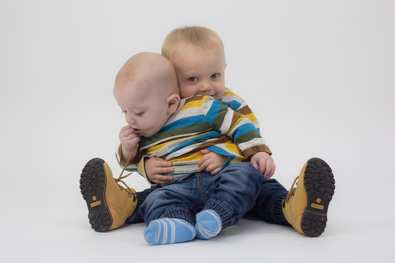 Cute baby brothers cuddling together studio portrait