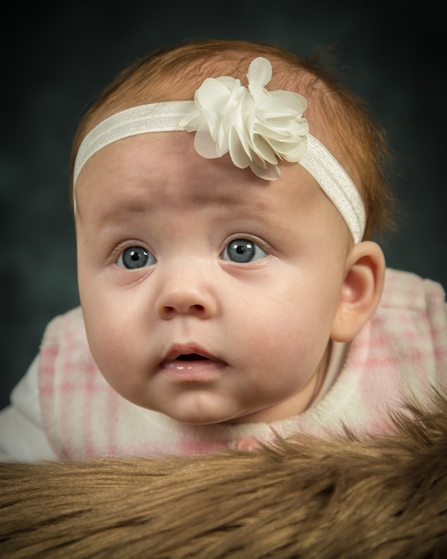 Cute baby girl with bow headband on fluffy cushion studio portrait