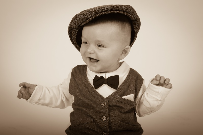 Happy toddler boy in waistcoat and cap - old time sepia photograph