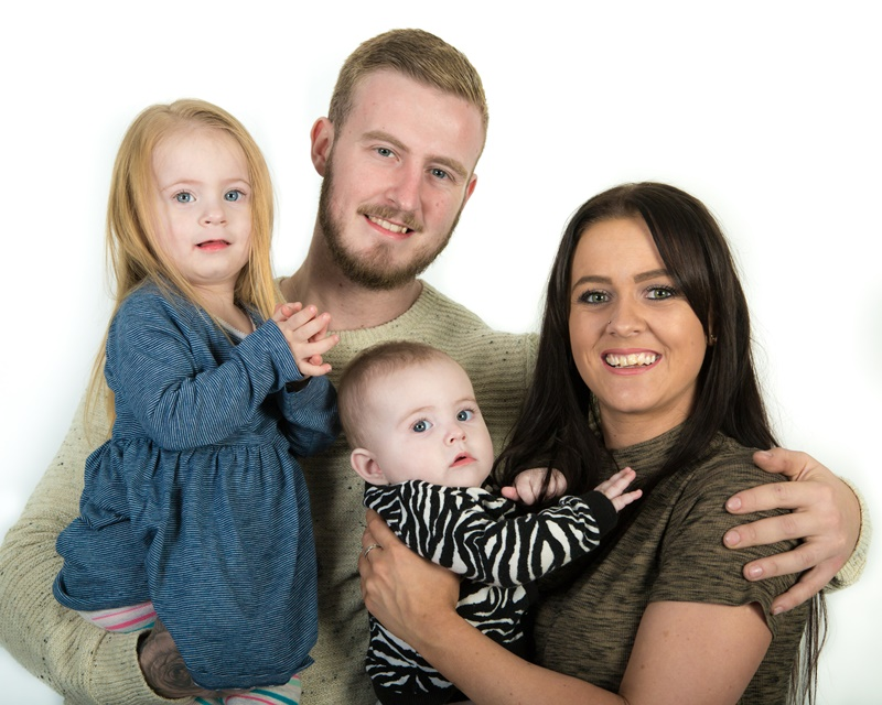 Happy young family with toddler and baby studio portrait
