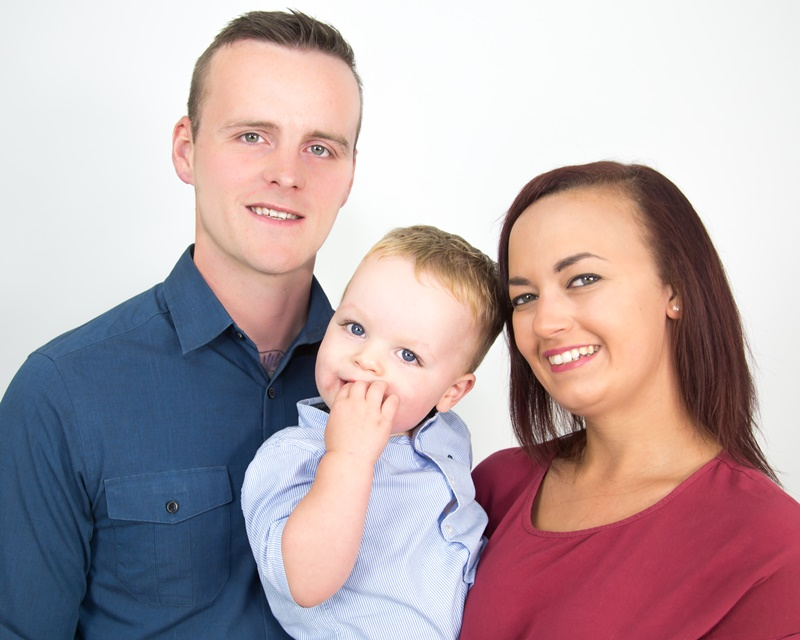 Happy young mom and dad with toddler son studio portrait